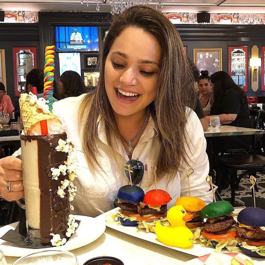 imagem de uma moca provando os hamburgueres e o milkshake da sugar factory