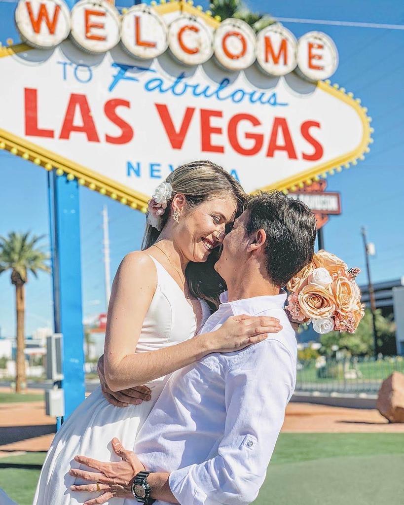 imagem de um casal feliz fazendo seu casamento em las vegas em frente ao letreiro de vegas